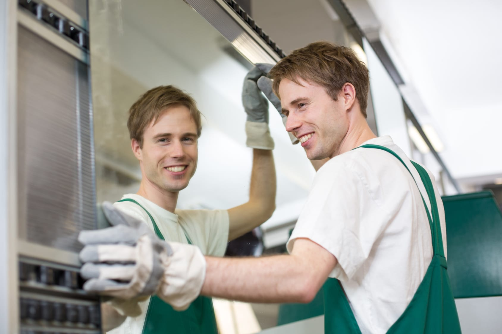 Worker in glazier's workshop putting glass in grinding machine